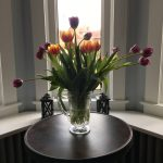 vase of fresh orange and purple tulips
